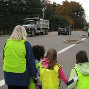 Kids with parents at an intersection waiting for traffic, learning see and be seen